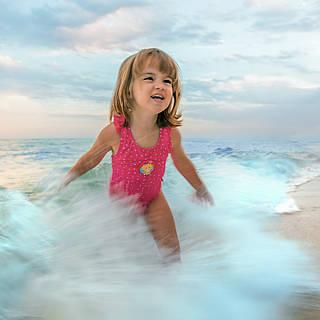 Kleines Mädchen badet im Meer