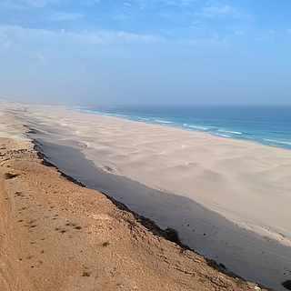Wüstenartiger Strandabschnitt der auf feinen Sand und blaues Wasser trifft unter blauem Himmel