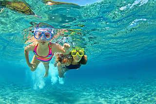 Mädchen beim Schnorcheln in glasklarem Wasser