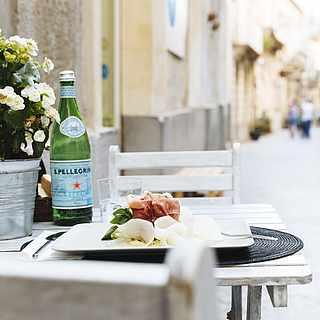 Gedeckter Tisch mit Wasser und Schinken in einer hübschen Gasse in Italien