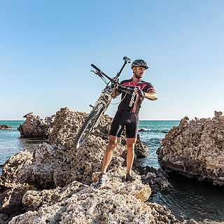 Mann beim Biken am Meer