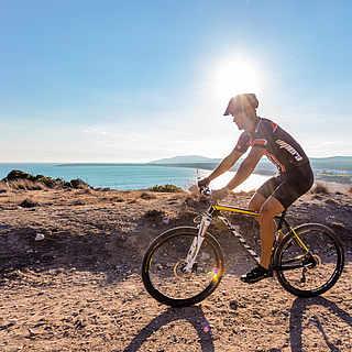Mann fährt Mountainbike am Meer