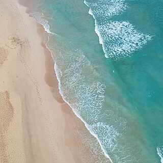 Blick von Oben auf türkises Meer und feinen Sandstrand