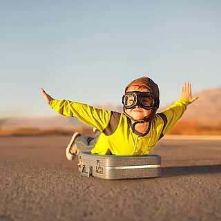 Verkleidetes Kind macht den Flieger auf einem Koffer