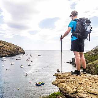 Mann in Nordic Walking Ausrüstung blickt von einem Berg über eine azurblaue Bucht