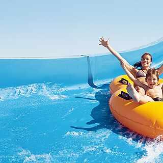 Frau und Kind auf gelben Ringen in einer blauen Wasserrutsche