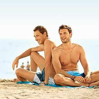 Schwules Paar sitzt gemeinsam am Strand
