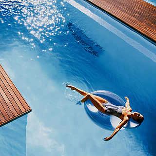 Frau mit Schwimmring im Pool.