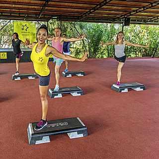 Menschen beim Step Aerobic in einer Grünanlage