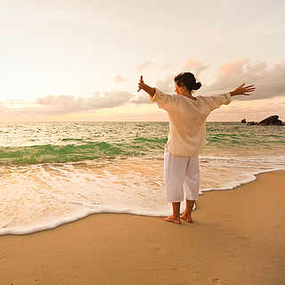 Frau Mitte 40 genießt Zeit am Strand.