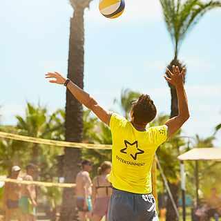 Mann holt zum Schlag aus beim Beachvolleyball draußen