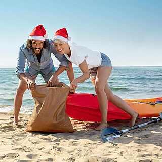 Pärchen am Strand mit Weihnachtsmützen und Jutesack