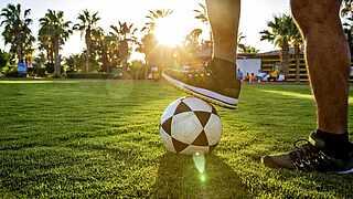 [Translate to English (en_EN):] Spieler mit Fußball unterm Fuß auf gepflegtem rasen mit Palmen